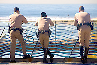 "California Highway Patrol Officers take in the view from, ""The Wave Fence"" (part of California Wash: A Memorial by Newton and Helen Mayer Harrison) on Thursday, January 26, 2012. The officers are on security detail for a foreign diplomat who is staying at Shutters beach hotel.."