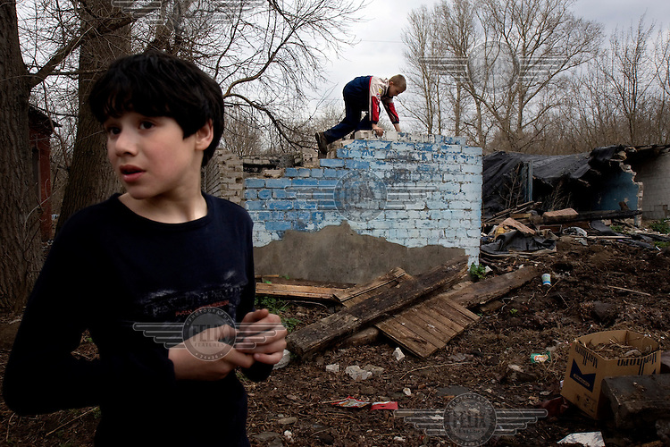 Children play in a crumbled house in the town of Tver.