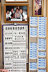 """A photo of former Japan Prime Minister Yukio Hatoyama hangs above  the business registration certificate and employee time card holder of Harumiya Co.'s """"Yakata-bune"""" pleasure boat business in Tokyo, Japan on 31 August  2010. Photographer: Robert Gilhooly"""