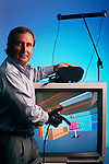 Virtual or artificial reality. Alvar Green, CEO of Autodesk in 1990, Playing Cyberspace, a sophisticated videogame designed by AutoDesk Inc., USA. The computer monitor displays an image of one of Cyberspace's virtual (non-real) environments - a room - into which the player enters by wearing a headset & data glove. Two video images of the environment fit are projected into the eyes, whilst physical interaction is achieved through spatial sensors in the headset & optical fibers woven into the black rubber data glove, which send data to the computer on the player's position & movements in space. Alvar Green Model Released (1990)