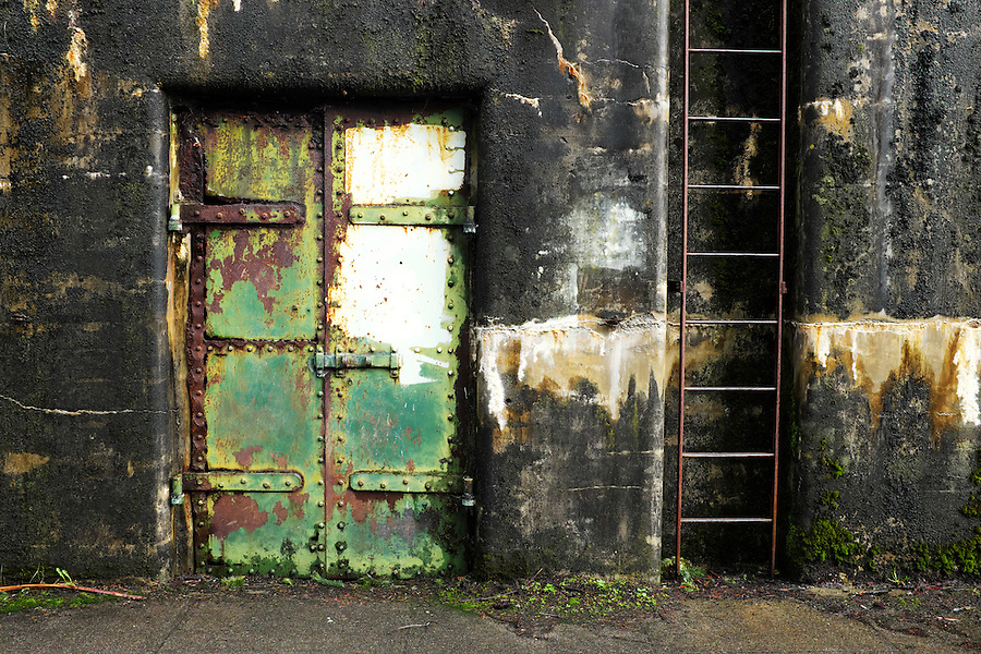 Closed rusty green steel door and ladder on concrete bunker tunnel, Artillery Hill, Fort Worden State Park, Port Townsend, Washington, USA