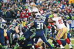 San Francisco 49ers running back Anthony Dixon (24) leaps over the Seattle Seahawks  defensive line to score yard touchdown in the 2nd quarter in the NFL  Championship Game at CenturyLink Field in Seattle, Washington on January 19, 2014.  ©2014. Jim Bryant Photo. ALL RIGHTS RESERVED.