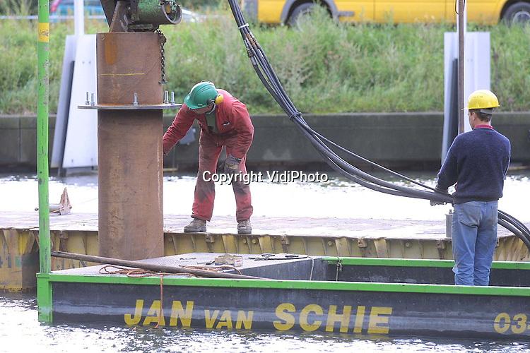 Foto: VidiPhoto..UTRECHT - In de 'hofvijver' van het provinciehuis in Utrecht is dinsdagmiddag met een hoogwerker het eerste draaiende beeld van Nederland geplaatst. Ieder kwartier draait de beeldengroep en kwartslag. Een enorme roestvrijstalen pijp dient als sokkel en moest in de vijverbodem getrild worden. Het bronzen kunstwerk is van de bekende kunstenaar Jits Bakker en toont een man en een vrouw die elkaar de hand reiken: het symbool van een bestuurder die contact legt met een burger. Maandag wordt het kunstwerk, dat bjna 2 ton heeft gekost, onthuld.