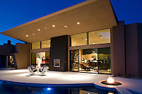 Night time shot of ultra modern home across swimming pool