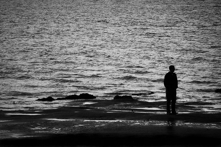 A lone silhouetted man standing on the beach and staring into the ocean.