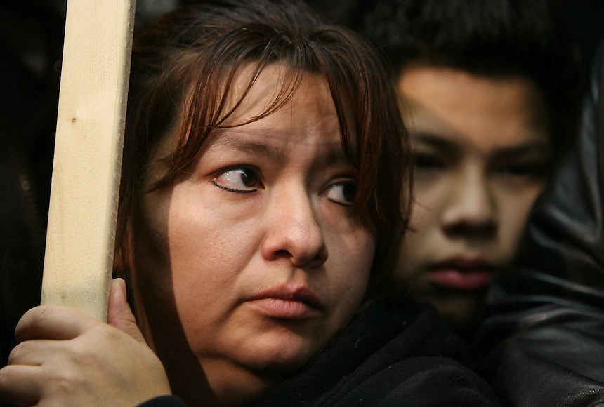 Patricia Robles and her son, Armondo, Jr., listen during a press conference held by Jesse Jackson in the lobby of Republic Windows & Doors, 1333 N. Hickory Av. on Chicago's near north side, Sunday, Dec. 7, 2008. Workers are having a sit-in after all were laid off a few days ago.  (AP PHOTO/Eric Y. Exit)