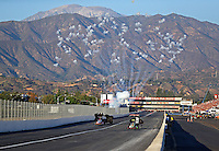 Nov 13, 2016; Pomona, CA, USA; Fireworks explode as NHRA top fuel driver Doug Kalitta (left) defeats teammate J.R. Todd to win the Auto Club Finals at Auto Club Raceway at Pomona. Mandatory Credit: Mark J. Rebilas-USA TODAY Sports