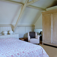 A simple yet feminine bedroom has been created in this attic room