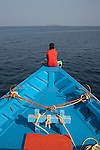A fisherman from the Maldives sits making a call on his mobile cell phone on the bow of a dhoni boat which heads along on a calm Indian Ocean. After a hard day's fishing he gazes forward to open sea where an almost uninterrupted view of sea and horizon is seen beyond except for a small island is faintly in view. Even small remote atoll communites in the Maldives have strong phone signals and many also have good Wi-Fi connections. He and his crew have been catching Yellow Fin Tuna in the seas north of the capital Male in this Islamic Republic. Their catch is for export to the EU and in particular, the UK's supermarkets. There is no limit and no obvious destination, just infinity and the thought of tomorrow.