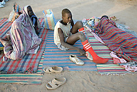 Young competitors wake from a night under a blanket at the Twic Olympics in Wunrok, Southern Sudan.