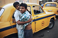 Men involved in a drunken dispute on the streets of Kolkata. The The yellow Ambassador taxi is still ubiquitous in Kolkata...Photo: Tom Pietrasik.Kolkata, West Bengal. India.February 17th 2009