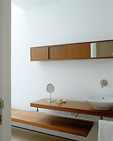 Counterbalanced open shelving in this contemporary bathroom is both functional and stylish