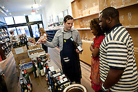 An employee advises customers at Chambers Street Wines in New York, NY, USA, 22 May 2009. The store specializes in naturally made wines from artisanal small producers and has received a Slow Food NYC Snail of Approval.
