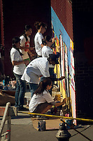 Volunteers with New York Cares paint a mural on the side of PS 33 the Chelsea School in New York on October 20, 2007. (© Richard B. Levine)