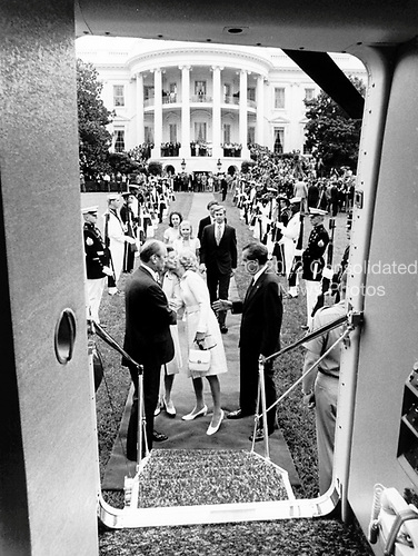 First lady Pat Nixon kisses Betty Ford good-bye as she and United States President Richard M. Nixon prepare to board Marine 1 for their departure from the White House following Nixon's farewell statement in the East Room on August 9, 1974. Vice President Gerald R. Ford looks on from left and President Nixon looks on from the right.  Nixon's daughters Tricia and Julie and their husbands are in the background waiting to board Marine 1 with their parents.<br /> Credit: White House via CNP