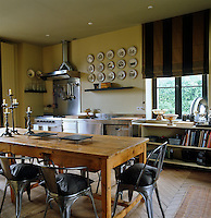 This country kitchen is furnished with an old pine atelier table and chairs which are re-editions of a 1930s design