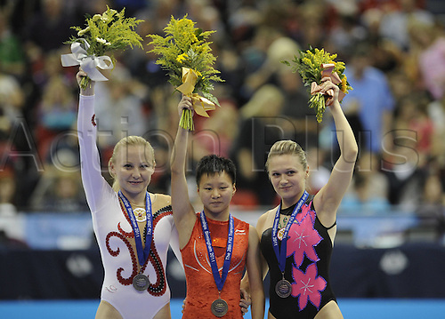 20.11.2011. Birmingham England. Jia Fangfang of China, Anna Korobeynikova of Russia and her teammate Anzhelika Soldatkina pose on The winners Podium After the womens Tumbling Individual Final of The 2011 trampoline and Tumbling World Championships in Birmingham Britain. Jia Fangfang of China Won with 71,700 Points with Russians Anna Korobeynikova and Anzhelika Soldatkina Ranking Second and Third
