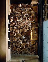 The dry-packed sandstone wall gives this indoor shower an outdoor feel