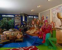 Portrait of fashion designer Zandra Rhodes sitting in her colourful open-plan living area