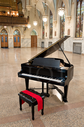 A black grand piano waits for someone to accept its invitation to come and play in this beautiful old church, one that has been converted to a social hall and concert venue. A red sash highlights the bench with a splash of color, and the soundboard shows gold inside the dark case. <br />