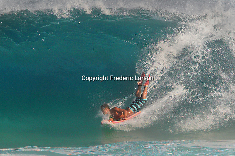 A boarder drops into a wave at Sandy Beach in Hawaii during high-tide makes for huge breaking waves close to shore.