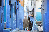 Man wearing a djellaba and woman wearing a hijab, walking in a narrow street painted blue in the medina or old town of Chefchaouen in the Rif mountains of North West Morocco. Chefchaouen was founded in 1471 by Moulay Ali Ben Moussa Ben Rashid El Alami to house the muslims expelled from Andalusia. It is famous for its blue painted houses, originated by the Jewish community, and is listed by UNESCO under the Intangible Cultural Heritage of Humanity. Picture by Manuel Cohen