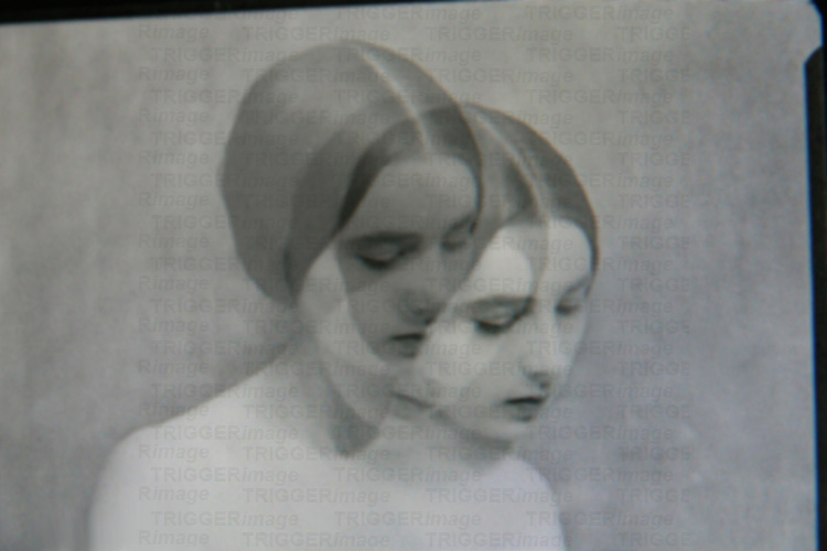 A young woman's face looking down in a triple exposure