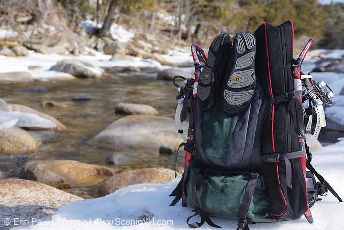 Snowshoes & water shoes strapped to backpack next to the East Branch of the Pemigewasset River in the Pemigewasset Wilderness of Lincoln, New Hampshire USA during the winter months.