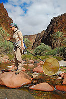 An entomologist with a collecting net on a wadi in Socotra, Yemen.