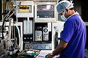A anesthetist seen next to the machines manning the patient during  an open heart surgery at operation theatre of the Narayana Hrudayalaya in Bangalore, Karnataka, India. Photo: Sanjit Das/Panos