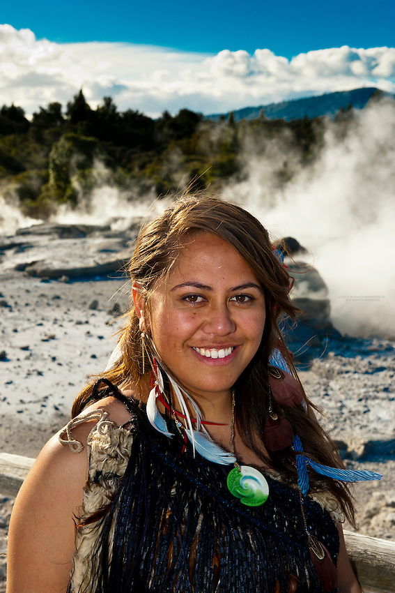 A young Maori woman (with the Pohutu Geyser behind), Te Puia (New Zealand Maori Arts &amp; Crafts Institute), Rotorua, New Zealand