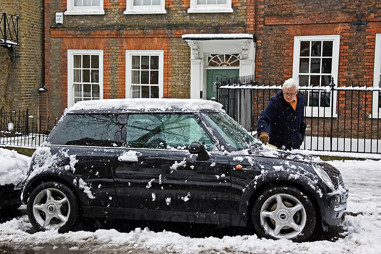 Man scrapes snow off Mini Cooper car parked in London street, Church Row, Hampstead, England, UK