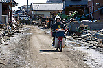A postman on a Japan Post motorbike drives through the rubble  in Higashi Matsushima, Miyagi Prefecture, Japan on  23 March 20011.  Some 350 motorcycles 160 four-wheel vehicles were destroyed by the magnitude 9 earthquake and tsunamis that swept through Japan's northeast on March 11. Photographer: Robert Gilhooly