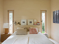 A shelf built into the wall behind the bed acts as a headboard and a place to display artwork and store books