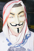 "A man wears a Guy Fawkes mask in the protest area outside the secure convention area on the final day of the Democratic National Convention at the Wells Fargo Arena in Philadelphia, Pennsylvania, on Thurs., July 28, 2016. The mask has been popularized by the movie ""V for Vendetta"" and the online group Anonymous."