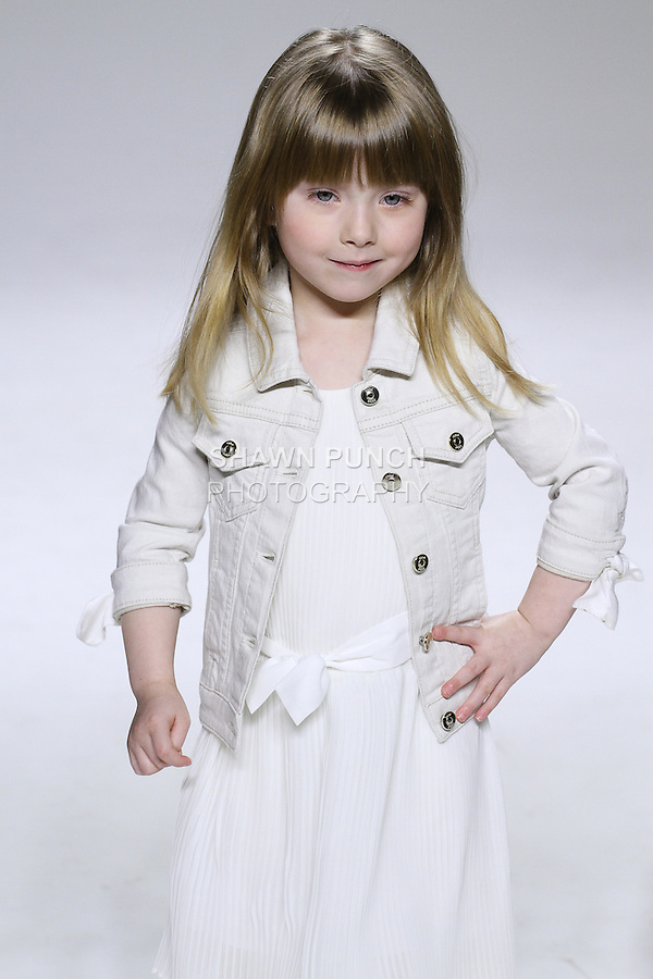 Young model walks runway in an outfit from the Chloe Spring Summer 2015 collection by Clare Waight Keller, at petitePARADE Spring Summer 2015, during Kids Fashion Week in New York City, on October 18, 2014.
