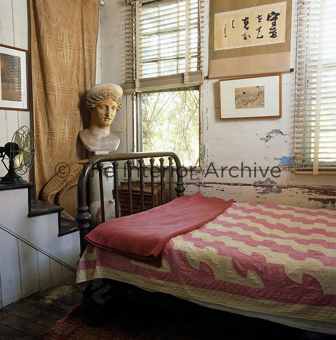 A wrought-iron bed and bust take up most of the available space in this tiny bedroom with crumbling walls