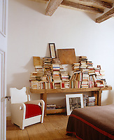 Books are kept in piles on the rustic table in this bedroom for the pleasure of pulling them out experimentally