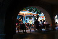 People eat in street cafe under arch in Girona, Spain