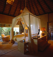 The four-poster bed stands in the centre of this high-ceilinged bedroom and is tented with a suspended mosquito net
