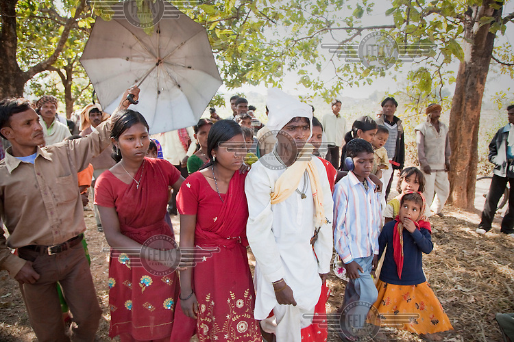 Sunil Tudu, in white, is led by his family through his bride-to-be's village on their wedding day: One of the wedding traditions of the Santhal Adivasi tribal people..
