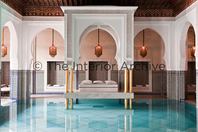 Relaxing areas with cushions in the alcoves frame the indoor ozone-heated pool