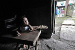 A child watches its family in the doorway of their house in the Guatemalan village of Santa Elena, located in the Peten region along the Salinas River where it forms a border with Mexico.