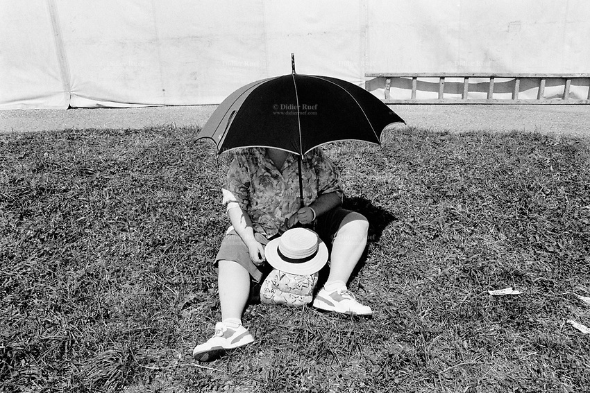 """Switzerland. Canton Jura. Saignelégier. A woman, seated on the grass, protects herself from the sun by covering her face and chest with an umbrella during the """"Marché-Concours"""", a horses' fair . © 1991 Didier Ruef"""
