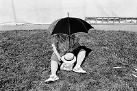 "Switzerland. Canton Jura. Saignelégier. A woman, seated on the grass, protects herself from the sun by covering her face and chest with an umbrella during the ""Marché-Concours"", a horses' fair . © 1991 Didier Ruef"