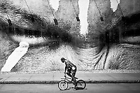A biker passes by a huge collage from the artist JR on Houston Street, New York