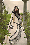 A beautiful young woman standing alone in renaissance dress and a cloak stands in a gazebo surrounded by plants outdoors
