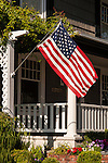 Home with American Flag on porch with yard and ideal neigborhood rural street scene