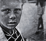 Close up of a young boy's face wearing a chain and striped shirt