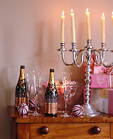 A large silver candelabra sits next to presents and a pair of champagne bottles on a wooden sideboard